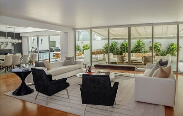 Using large scale sliding aluminium doors as a wall works wonders for opening up a living room, allowing a lot of natural light to fill the space and filter through the property.